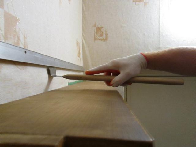 Заправка полотна над шкафом выполняется длинным шпателем