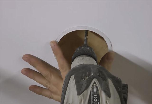Отверстие в перекрытие сверлится через кольцо в натяжном потолке