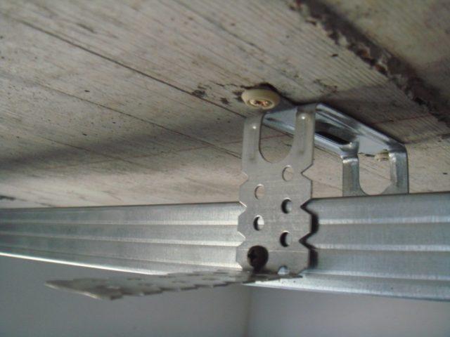 Принцип крепления профиля к потолку с помощью металлических подвесов